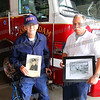 Bill holds a department  photo of himself as a young firefighter