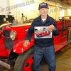 "Bill ""Tex"" Armstrong holds a photo of himself driving the firetruck in a city parade"