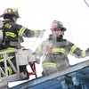 Firefighters Chris Yager and Eric Hendricks check the roof