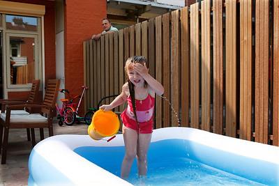 Nederland, Amsterdam, 24 mei 2007. gerenoveerde woning in de bloemenbuurt in amsterdam noord. meisje speelt in plastic zwembad in de tuin. buurman kijkt over de schutting. Foto: Katrien Mulder/Hollandse Hoogte