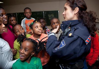Nederland, Amsterdam, 30 maart 2009. politievrouw in gesprek met groep surinaamse kinderen in de bijlmer, foto: Katrien Mulder