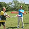 Anthony Yevoli shows Assemblyman Angelo Santabarbara how to use a Lacrosse stick