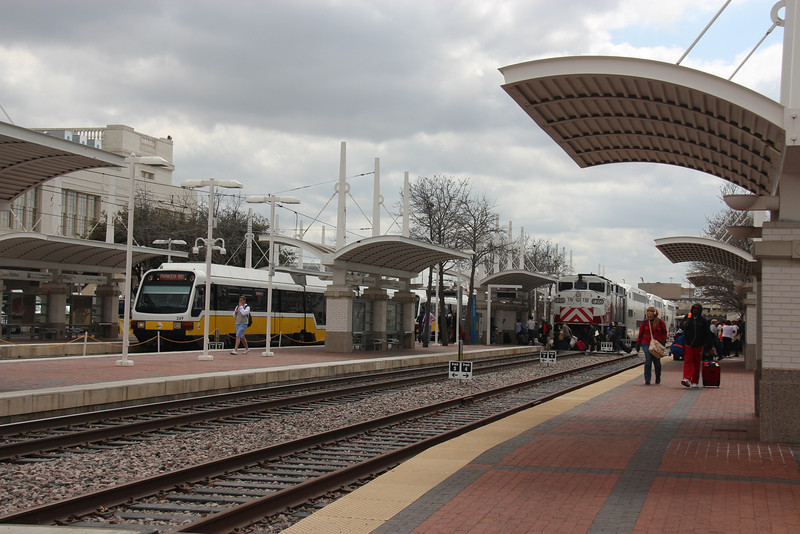 A DART train (on the left) and a TRE train are shown on the platform.