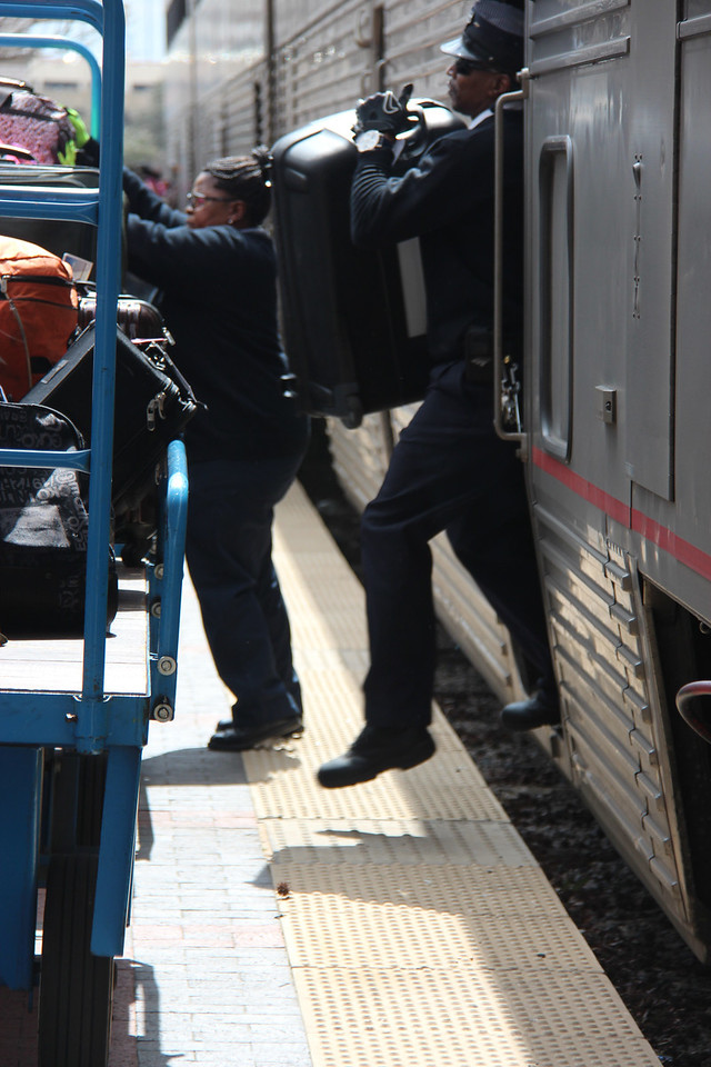 Conductor Mayo loads a suitcase onto the baggage cart.