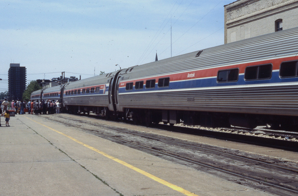 A large group of passengers is shown boarding a Chicago-bound 300 Series Train at Springfield, IL.