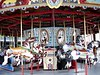 "A closer look at the carousel.  It does not have a band organ, but it does operate an older music playing device clearly marked ""John J. Fanelli Amusements""."