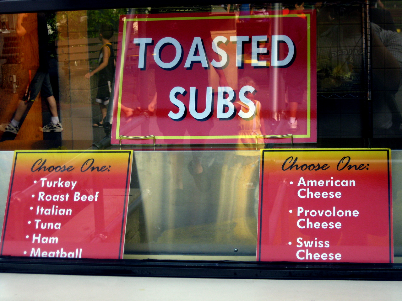 Sub sandwich signs at the Pizza Ria food stand.