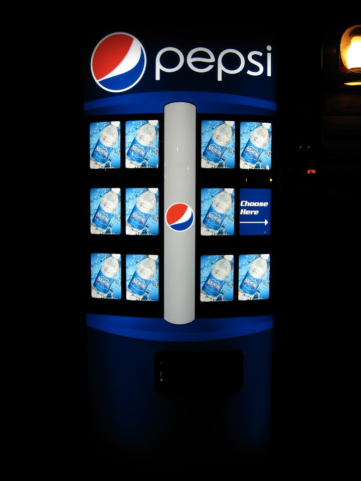 An Aquafina machine at night.