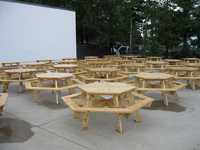 A flotilla of new wooden tables.