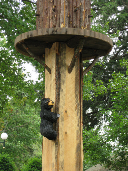 There's a little bear climbing the birdhouse pole!