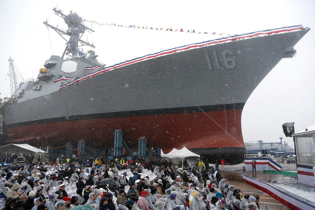 . The future USS Thomas Hudner, a U.S. Navy destroyer named after Korean War veteran Thomas Hudner, looms over the audience during a christening ceremony at Bath Iron Works in Bath, Maine, Saturday, April 1, 2017.  Hudner, a naval aviator who crash-landed his plane to try to save a downed pilot in the Korean War was honored with a ship bearing his name. (AP Photo/Mary Schwalm)