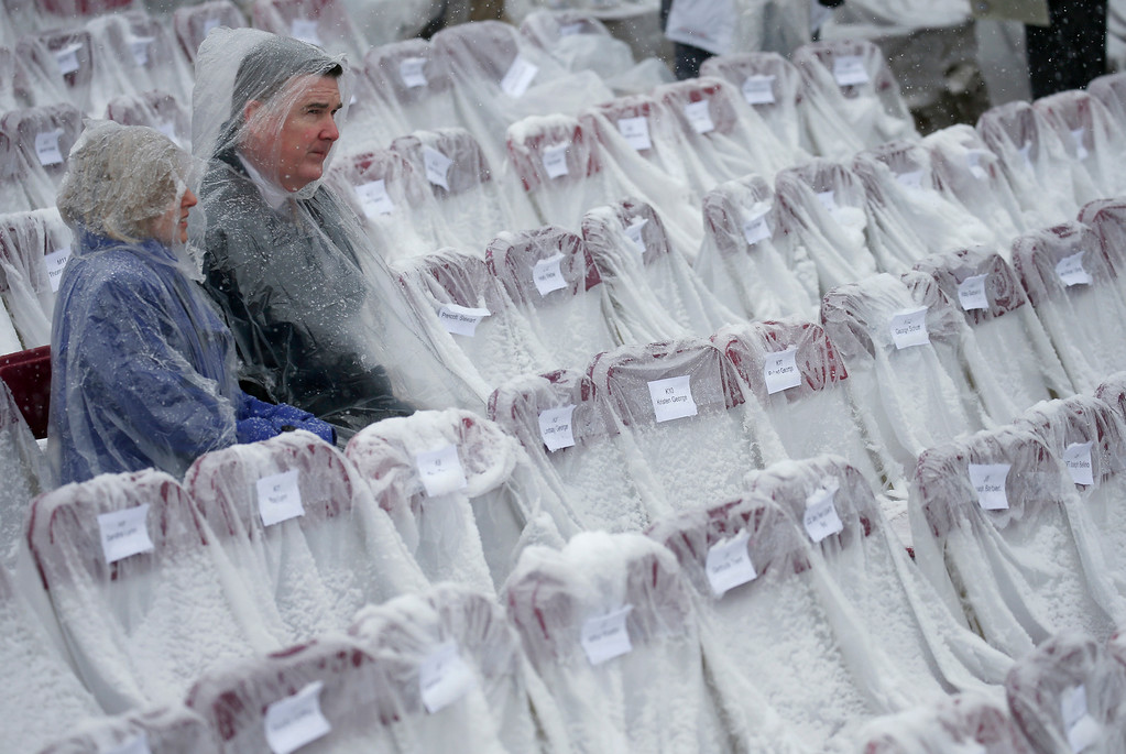 . Spectators sit amongst snow covered seats before the christening ceremony of the future USS Thomas Hudner, a U.S. Navy destroyer named after Korean War veteran Thomas Hudner, at Bath Iron Works in Bath, Maine, Saturday, April 1, 2017.(AP Photo/Mary Schwalm)