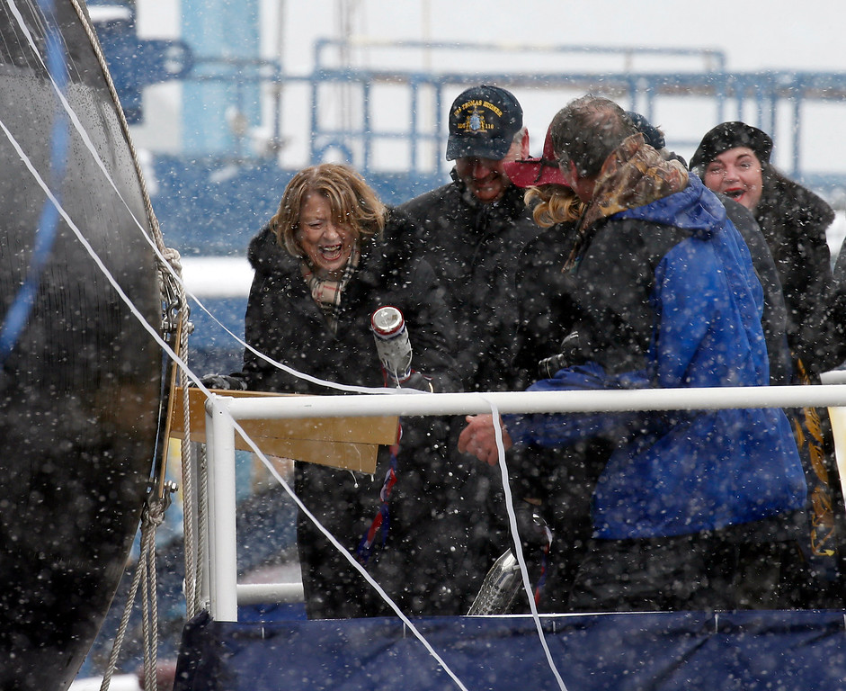 . Georgea Hudner, wife of Thomas Hudner, left, laughs as she struggles to break the champagne bottle during the christening ceremony of the future USS Thomas Hudner, a U.S. Navy destroyer named after her husband at Bath Iron Works in Bath, Maine, Saturday, April 1, 2017.   Hudner, a naval aviator who crash-landed his plane to try to save a downed pilot in the Korean War was honored with a ship bearing his name. (AP Photo/Mary Schwalm)