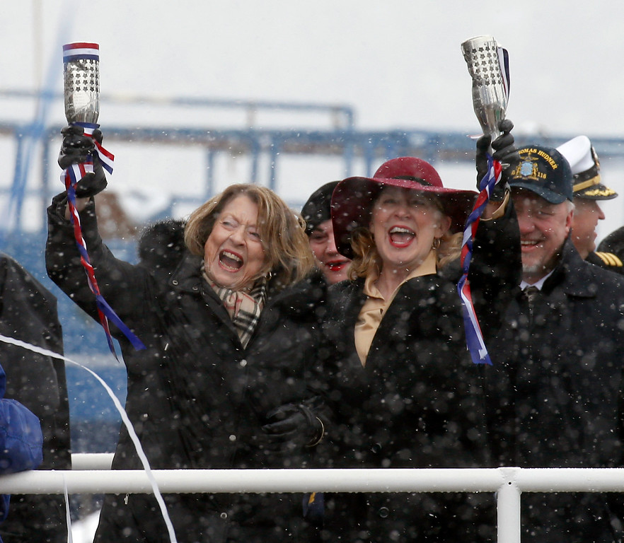 . Georgea Hudner, wife of Thomas Hudner, left, and Ship Sponsor Barbara Joan Miller, right, laugh, as they hold up their champagne bottles during the christening ceremony of the future USS Thomas Hudner, a U.S. Navy destroyer, at Bath Iron Works in Bath, Maine, Saturday, April 1, 2017.  Hudner, a naval aviator who crash-landed his plane to try to save a downed pilot in the Korean War was honored with a ship bearing his name. (AP Photo/Mary Schwalm)