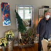 Owner Ken Lemanski stands next to a window box with white poinsettias and a great piece of art from Rahim Gray.