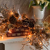 The fireplace mantle is adorned with gold and silver balls, pine cones and white poinsettias.