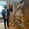 Mark Caputo shows off his flocked tree of metallic, gold and silver in the dining room.