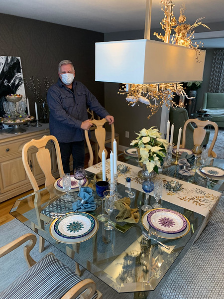 Ken Lemanski stands next to his dining-room table, festively decorated by Ken Lemanski of Winchester stands next to his festively decorated by Mark Caputo of Lowell.