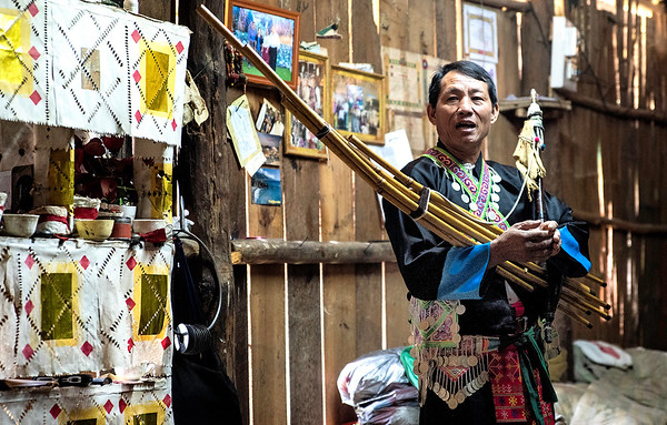 In his home Hmong man demonstrates costume worn for special occasions as well as an instrument he plays.