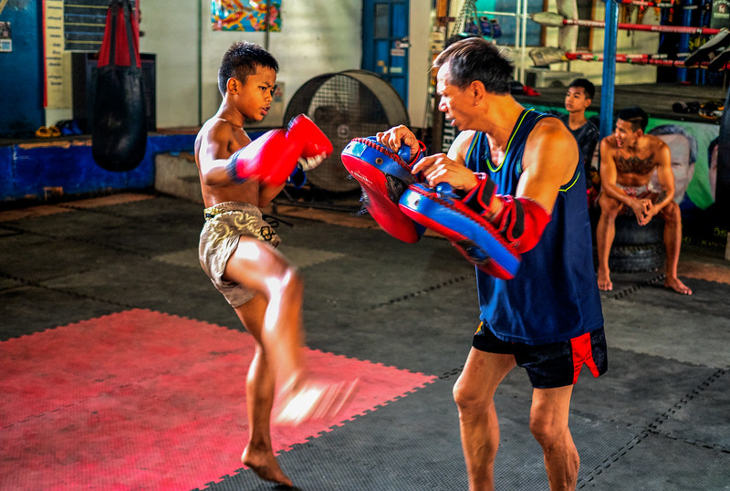 At at Bangkok facility for disadvantaged youths a boy learns Muay Thai, an-all limbs and all-tactics martial art.  He and others living and learning at the facility hope to become professionals in the sport.