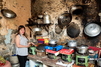 Housewife and lottery seller, Saigon. Shares 800-square-foot apartment with 23 other people, all family members. The 24 people are part of four related families. Each one has its own burner for preparing meals. There is only one toilet in the apartment.