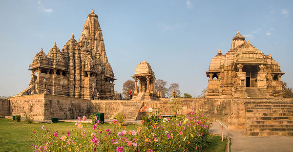 Part of the Hindu and Jain complex of temples in Khajuraho, India. Looking southwest, Kandariya Mahadev Temple is on the left,  Devi Jagadamba Temple is on the right. Famous for their numerous erotic carvings, most of the temples were built between 950 AD and 1050 AD by the Chandela dynasty.
