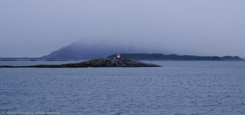 Fyrlykt utenfor Hamnes ved Skarstad i Efjord. I bakgrunnen sees Engelsøya og bak i snøværet sees Nordfjellet på Barøya. Foto 1. april 2021 fra moloen på Skarstad.