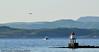 MS Sjøsprint på tur over fra Liland til Kjeldebotn med passasjerer som kom med fly fra Oslo. I bakgrunnen SAS-maskinen som returnerer, like etter avgang fra Narvik/Harstad Lufthavn, Evenes. I forgrunnen fyrlykt utenfor Kjeldebotn.
