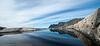 Senja. Okstindan speiler seg i liten vannpytt på land. Foto fra Tungeneset.