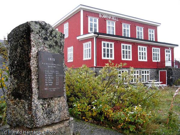 """Bjørnfjellhus, den tidligere turiststasjonen. I og utenfor her omkom i april 1940 flere norske soldater i kamper mot overlegne tyske styrker. Til venstre minnestøtte over falne i """"Trønderbataljon"""", IR 13."""