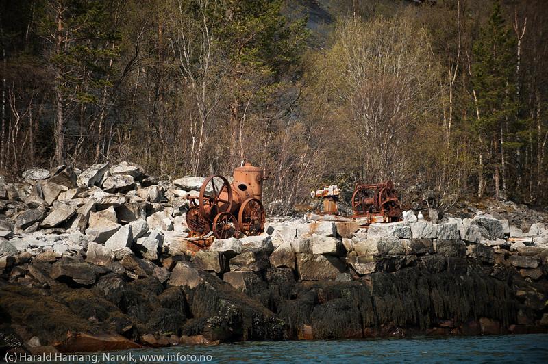 Gammelt steinbrudd på sørsiden av Skjomenfjorden. Midt på sees en såkalt Lokomobil, dvs, en transportabel dampmaskin. Det store hjulet er svinghjulet til dampmaskinen. Til høyre diverse spillverk. Disse står på utlastekaia der man sendte steinblokker til Narvik for bygging. Stein var et mye benyttet byggemateriale før betongen ble allment i bruk. Stenbruddene er delvis på venstre side av dette bildet, men primært på høyre side.