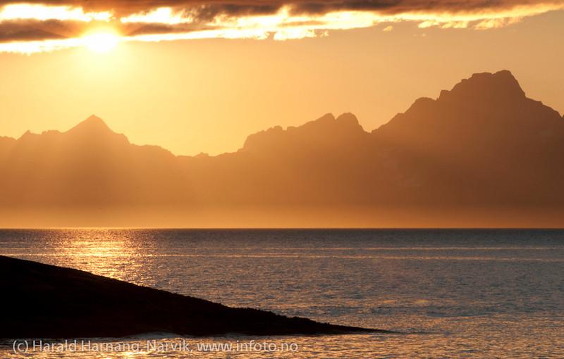 Tranøy i Hamarøy kommune, Nordland. Solnedgang i august, utstikt fra Tranøy fyr. Vesterålsfjellene i bakgrunnen.