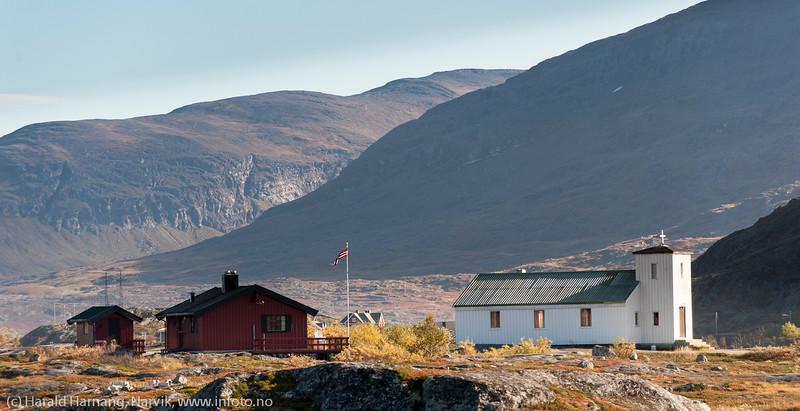 Hytter på Bjørnfjellplatået med kapell til høyre.
