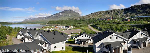 """Boligkomplekset """"Marie Pigg"""" på Riksgrensen på svensk side. Til høyre sees Ofotbanen og mellomriksveien samt hotellanlegget på Riksgrensen. Midt på campingvogner og spikertelt."""