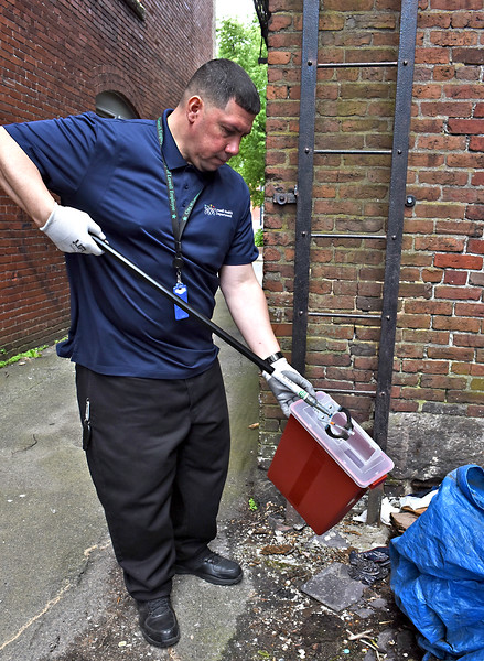 Andres Gonzalez Syringe Collection Program Coordinator for the Lowell Health Dept., places a needle in a haz-mat container. SUN/David H. Brow