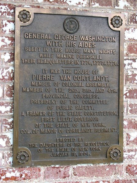 Bronze plaque on the front of the house.