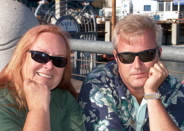 """Dee and Andy<br /> I requested that Andy not take any photos of me, that I'd pose for him if I could stand behind a heart... I caught him trying to sneak a shot once, and I'd bet he's got some but I hope he'll respect my vanity here... I read that there was a heart in<br /> front of Red's Java Hut on the Embarcadero and I figure I could hide behind that. Well, when we left the painted ladies to get to the other side of town, the map looked like the street crossed Market Street, but guess what, it didn't and I told Ed<br /> to turn right when in hindsight he should have turned left. Market Streed doesn't allow ANY turns, left or right until you run into the Mission District. Oh my, so Andy got a little of downtown, a little of the Mission district, Some of South of Market,<br /> China Basin, the Ball Park and I saw the words Java Hut and a driveway and we pulled in. I looked all over but couldn't find the heart! I asked at the Java Hut but couldn't quite catch what the friendly but English is my second language young man was trying to tell me. I got the gist of it's two blocks north. Well Andy had a good time looking at the boats and we got some soda and sat outside for awhile enjoying the ambience of a great weather day. Andy went on his way to have dinner with a friend and to follow it up with some night shooting. Sure enough two blocks north there was """"REDs"""" Java Hut and the heart!"""