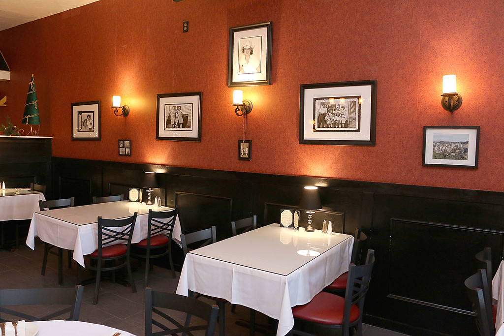 . A view of some of the dinning area at Angelina\'s Italian Restaurant in Tewksbury. The pictures on the wall are all owner Susan Amato\'s family. SUN/JOHN LOVE