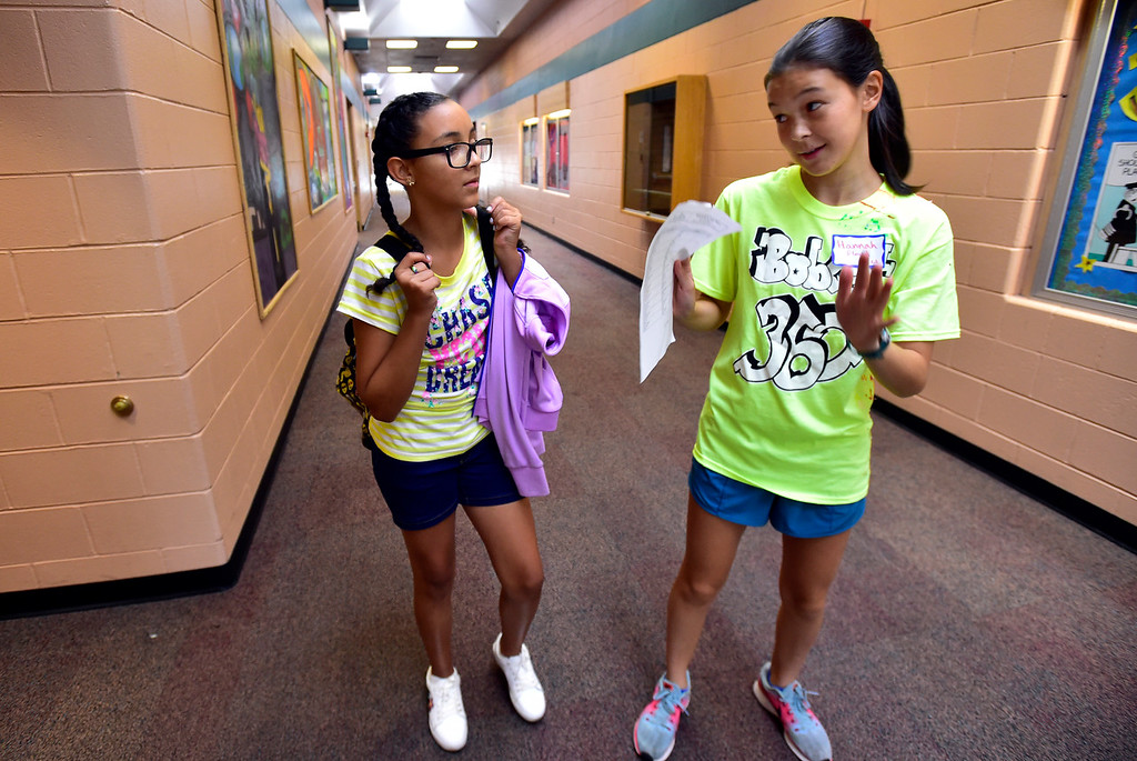 . LAFAYETTE, CO - AUGUST 15, 2018  Eighth grader Hannah Floyd, right, gives some advice on class schedules to sixth grader Niema Iarussi as she helps the new student tour the school during the first day of classes for sixth graders at Angevine Middle School in Lafayette on Wednesday August 15, 2018.  (Photo by Paul Aiken/Staff Photographer)