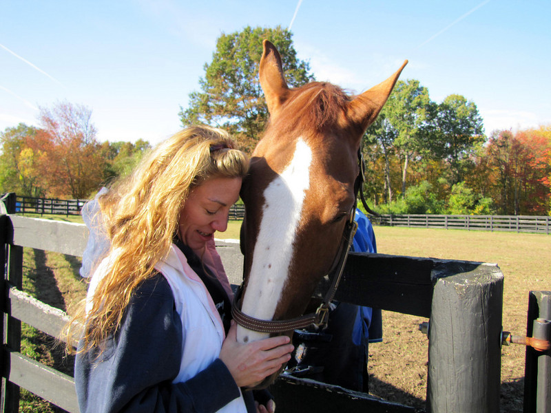 Cheri O'Reilly communing with a horse in the back paddocks