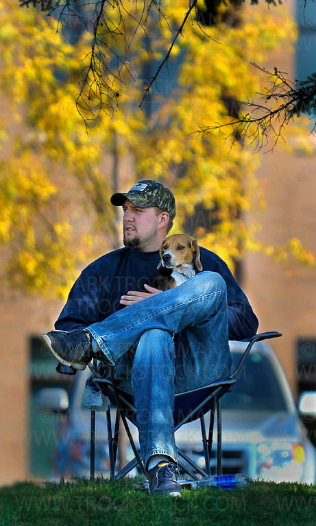 Grabbing a high, shady spot to watch the parade, Josh Moberg and his one-year-old Beagle, Maci, get all the warmth and none of the Sun's glare on a hot, stunning morning at the 2012 Plymouth on Parade Festival Saturday, Sept. 29, 2012.