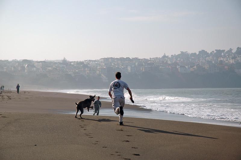 Ein Mann und sein Hund laufen den Strand von Baker Beach in San Francisco entlang.