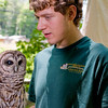 A portrait of Eric, a student intern, with Barry the Barred Owl (strix varia) at the Blue Ridge Wildlife Institute at Lees-McRae College in Banner Elk, NC.