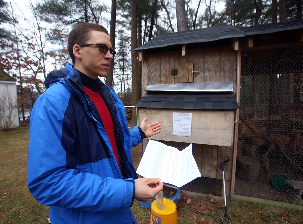 . Alexander Melville of Chelmsford with his family\'s chicken coop. Under new town regulations, they face costs including $1,500-2,000 for a plot plan. (SUN/Julia Malakie)