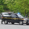 Fitchburg Police and Massachusetts Environmental Police blocked off part of Nashua Street in Fitchburg on Thursday afternoon while a bear cub was perched in a tree in the woods. Police had been chasing the bear throughout the city for a few hours. SENTINEL & ENTERPRISE / Ashley Green