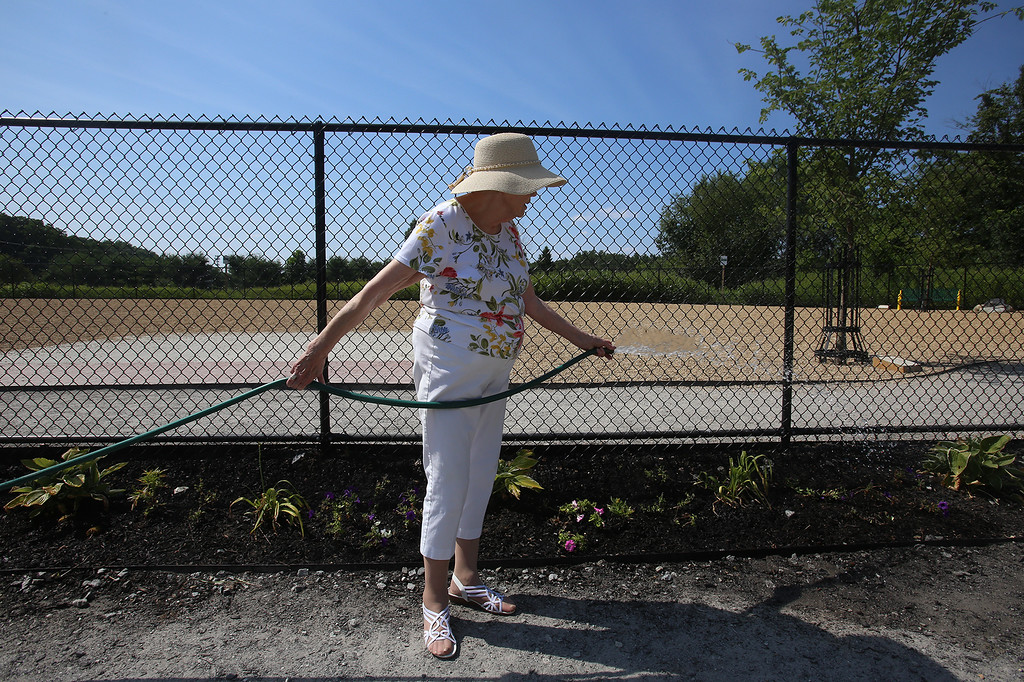 . Shirley Holdman of Billerica, with the Friends of the Billerica Dog Park Committee, waters the plants at the recently opened Billerica Dog Park. (SUN/Julia Malakie)