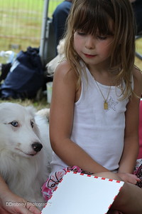 Ella taking advantage of some quiet time to listen to a story with a dog friend at the Tails of Joy tent.  Tails of Joy sponsors the R.E.A.D. - Reading Education Assistance Dogs.  Laura and I were able to raise $240 in portrait donations for this wonderful program!!  The ladies will use that money to buy books to send home with the children who read to the dogs.  ;-)