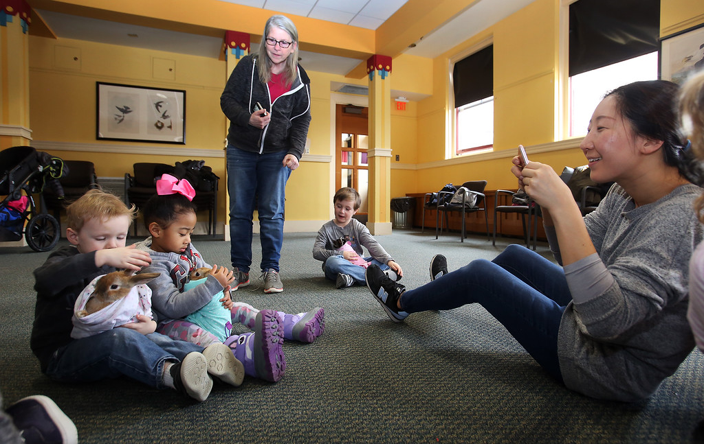 . Farm Visits brings their travelling petting zoo of baby farm animals to Pollard Memorial Library. Young Joo Eweka of Lowell takes a picture of her daughter Winslet Eweka, 3, and her friend Theodore Durkin, 3, of Lowell, holding baby bunnies. Bunnies ranged from 9-16 weeks old. (SUN Julia Malakie)