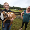 Opening of Indian Valley Goats Dairy at Krochmal Farms in Tewksbury. Kayleigh Nagle, 12, holds Tacoma, one of the Nubian goats born this year. At right is Erin Santos of Derry, N.H. (SUN/Julia Malakie)
