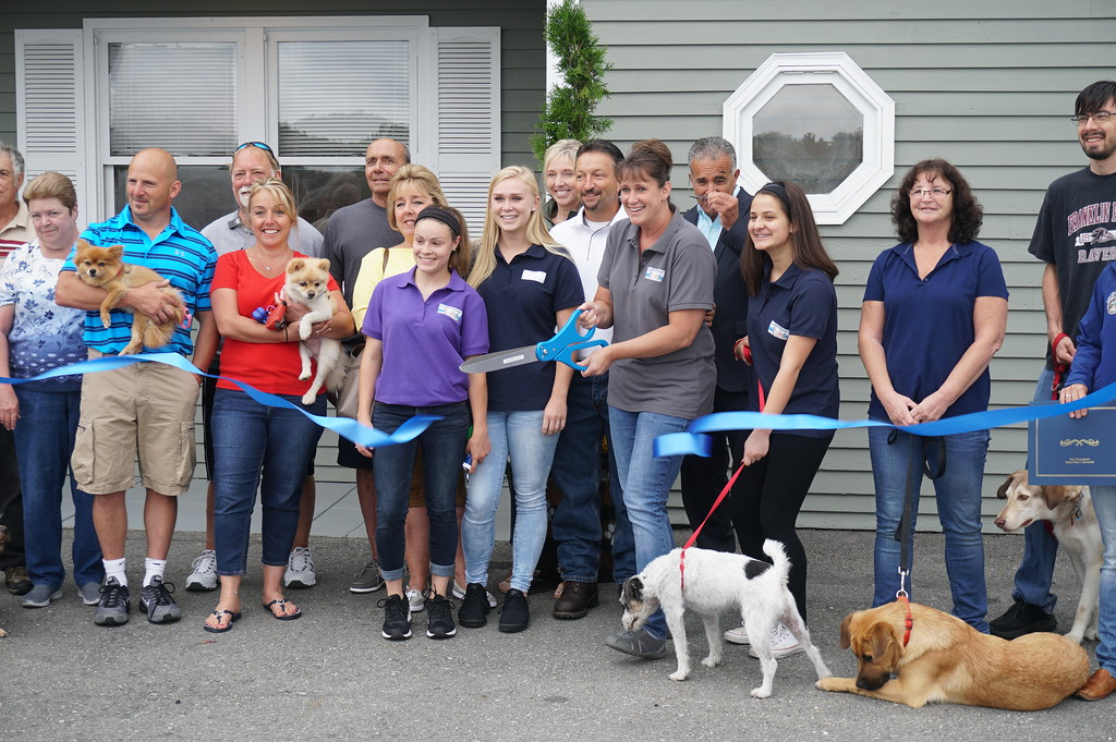 . Lakefront Dog Retreat owner Lena Grosser cuts the ribbon at Friday�s grand-opening celebration in Leominster.